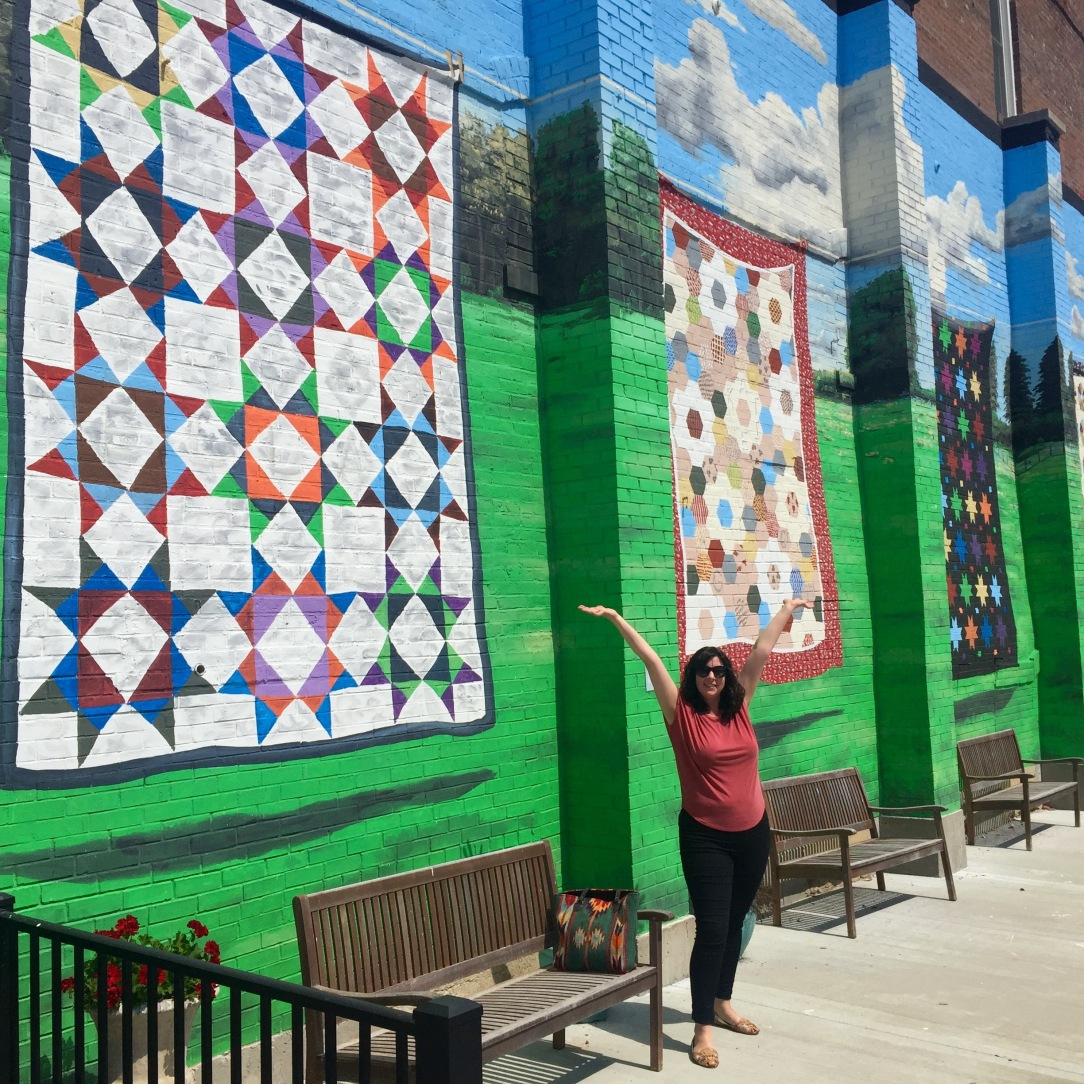 Laura in front of quilt mural
