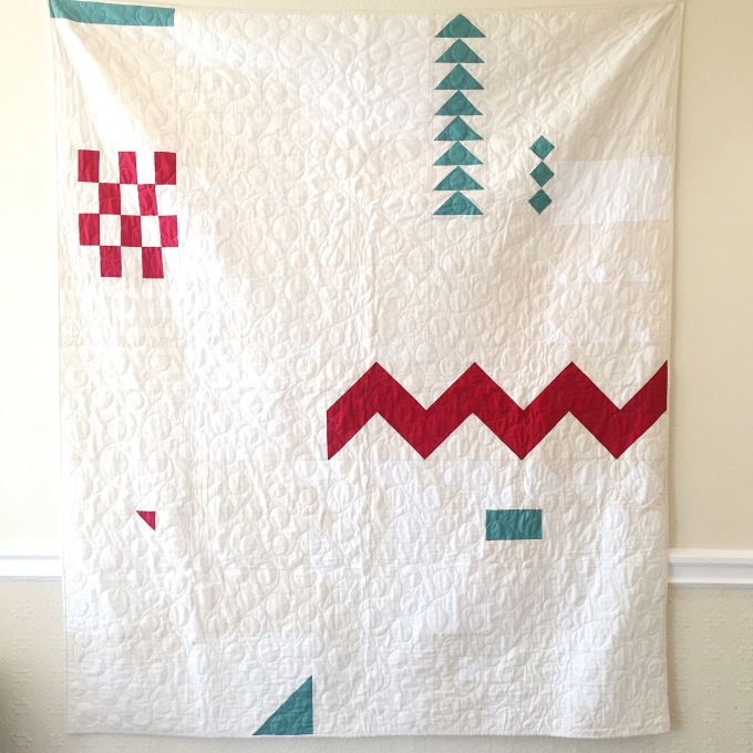 Full frontal picture of improve quilt hanging on the wall