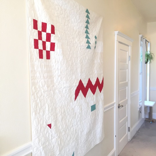 Improv quilt hanging up on the wall in a hallway